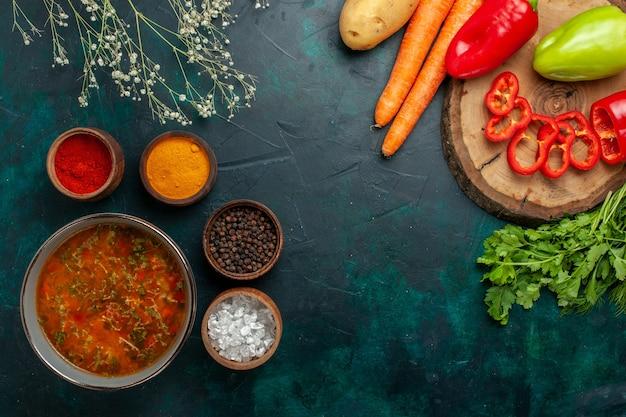 Draufsicht köstliche gemüsesuppe mit gewürzen auf grüner oberfläche lebensmittelgemüse zutaten suppenprodukt mahlzeit