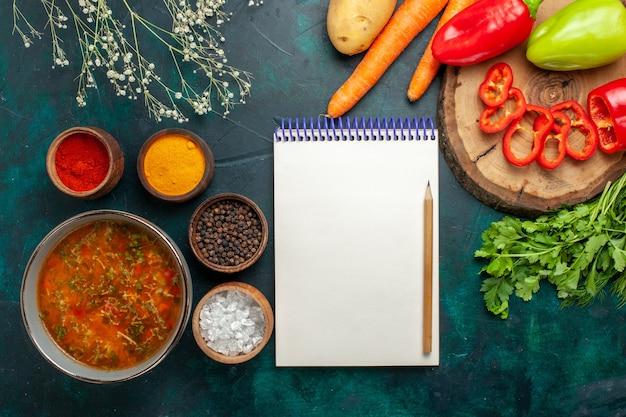 Draufsicht köstliche gemüsesuppe mit gewürzen auf grüner oberfläche lebensmittelgemüse zutaten suppenprodukt