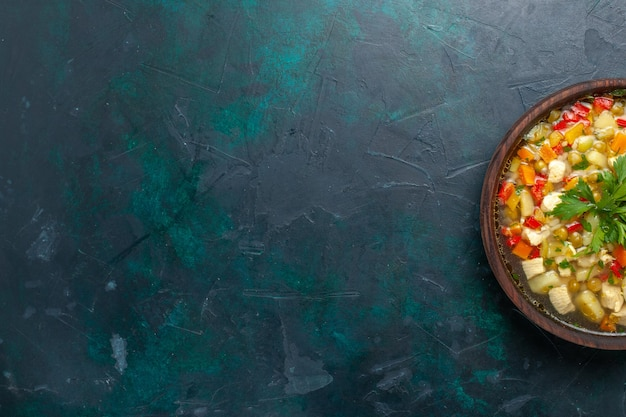 Draufsicht köstliche gemüsesuppe mit verschiedenen bestandteilen innerhalb des braunen topfes auf dunkelblauer schreibtischsuppe gemüsesauce mahlzeit essen heißes essen