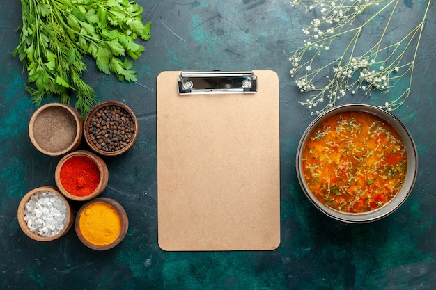Draufsicht köstliche gemüsesuppe mit verschiedenen gewürzen auf dunkelgrünem oberflächenlebensmittelmahlzeitgemüsesuppenzutatenprodukt