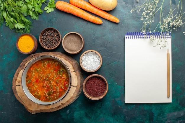 Draufsicht köstliche gemüsesuppe mit verschiedenen gewürzen auf dunkelgrünem schreibtischlebensmittelgemüsezutatensuppenproduktmahlzeit