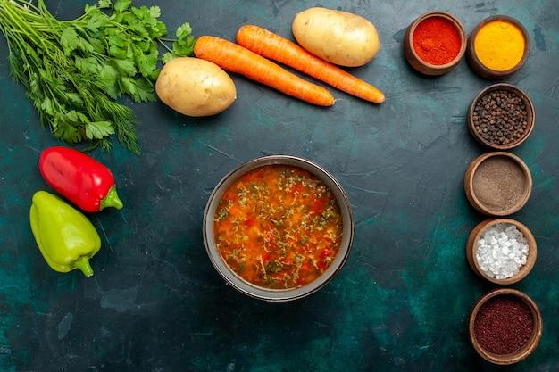 Draufsicht köstliche gemüsesuppe mit verschiedenen gewürzen auf dunkelgrünen oberflächenmahlzeitengemüsegemüsezutaten-suppenprodukten