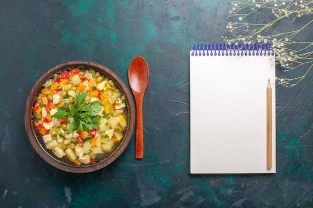 Draufsicht köstliche gemüsesuppe mit verschiedenen zutaten und notizblock auf dem dunklen schreibtisch suppe gemüsesauce essen warmes essen mahlzeit