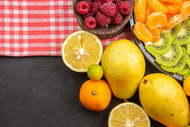 Draufsicht köstliche geschnittene früchte im teller mit frischen früchten auf dunklen früchten exotisches foto ausgereiftes gesundes leben des baumes