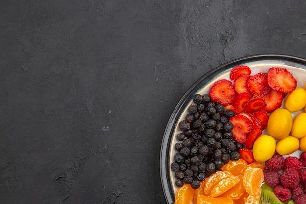 Draufsicht köstliche geschnittene früchte in der platte auf dunklem tropischem obstbaum exotische reife diätfotofreier platz