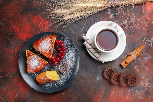 Draufsicht köstliche geschnittene torte mit keksen und tasse tee auf dunklem tisch süßer tortenkuchen