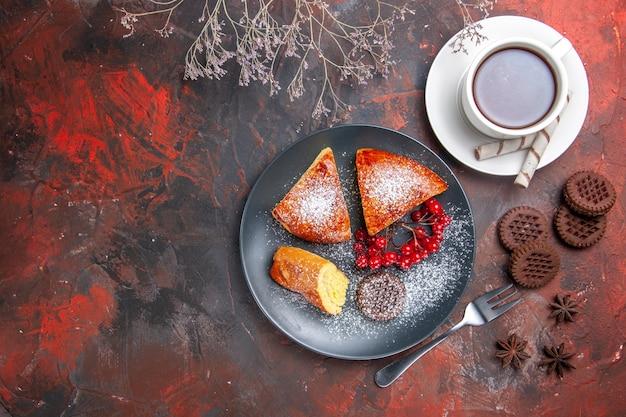 Draufsicht köstliche geschnittene torte mit roten beeren auf dem süßen tortentee des dunklen tischkuchens