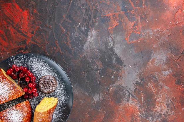 Draufsicht köstliche geschnittene torte mit roten beeren auf dunklem boden süßer tortenkuchen