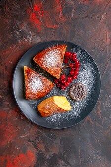 Draufsicht köstliche geschnittene torte mit roten beeren auf dunklem schreibtisch süßer tortenkuchen