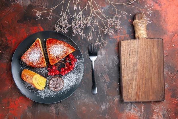 Draufsicht köstliche geschnittene torte mit roten beeren auf dunklem tischkuchen süßigkeiten torte