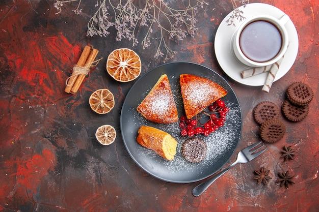 Draufsicht köstliche geschnittene torte mit tasse tee auf dem süßen tortentee des dunklen tischkuchens