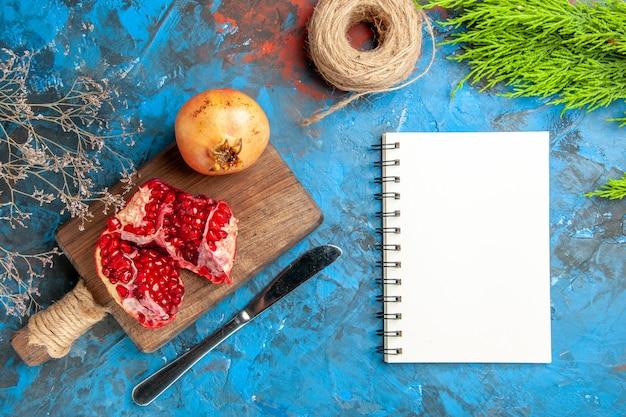 Draufsicht köstliche granatäpfel auf schneidebrett abendessenmesser ein notizbuch auf blauem abstraktem hintergrund