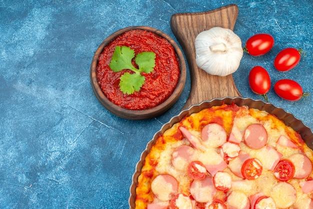 Draufsicht köstliche käsepizza mit würstchen und tomaten auf blauem hintergrund italienischer teigkuchen fast-food-fotofarbe