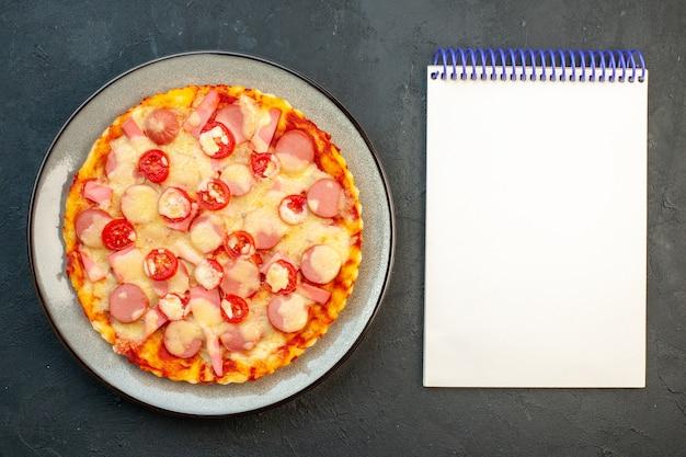 Draufsicht köstliche käsepizza mit würstchen und tomaten auf dunklem hintergrund italienischer lebensmittelteig-fast-food-fotofarbe