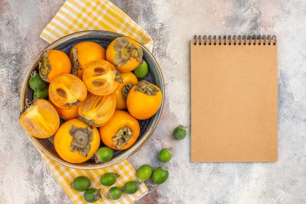 Draufsicht köstliche kaki in einem gelben küchentuch der schüssel feykhoas ein notizbuch auf nacktem hintergrund