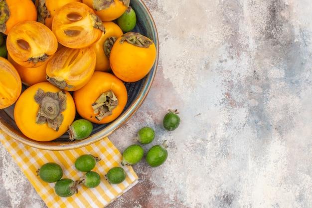 Draufsicht köstliche kaki in einem gelben küchentuch feykhoas der schüssel auf nacktem hintergrund