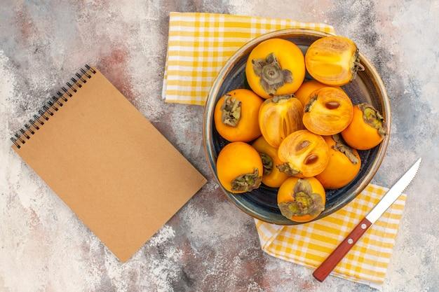 Draufsicht köstliche kaki in einem schüsselmesser gelbes küchentuch ein notizbuch auf nacktem hintergrund