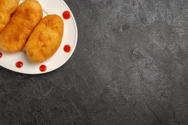 Draufsicht köstliche kartoffel-hotcakes innerhalb des tellers auf dunkelgrauem hintergrund