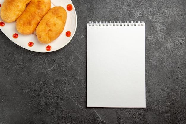 Draufsicht köstliche kartoffel-hotcakes mit notizblock auf dunklem hintergrund