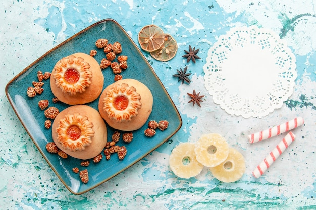 Draufsicht köstliche kekse mit bonbons auf der hellblauen hintergrundplätzchenkeks-süßen zuckerfarbe