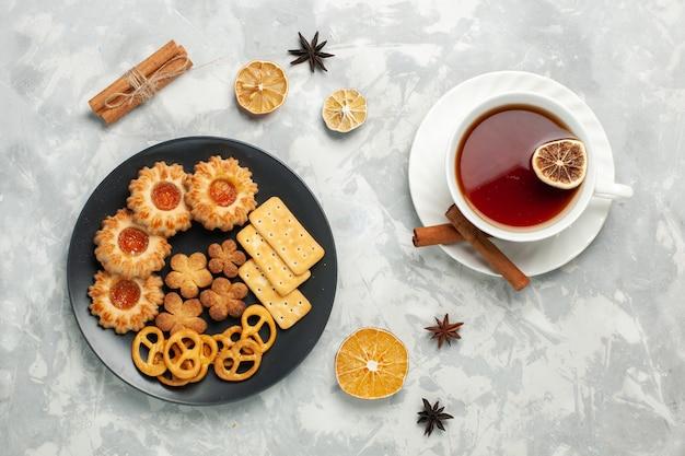 Draufsicht köstliche kekse mit crackern und chips in teller mit tasse tee auf dem hellweißen schreibtischkeks keks zucker süßer tee knusprig