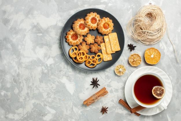Draufsicht köstliche kekse mit crackern und chips in teller mit tasse tee auf dem weißen schreibtisch keks keks zucker süßen tee chips