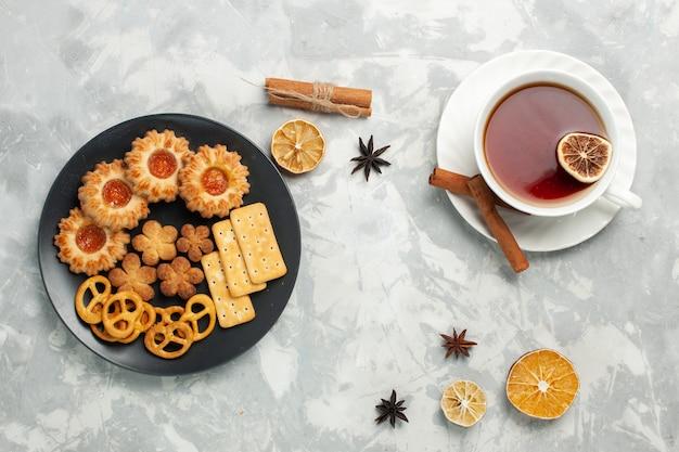 Draufsicht köstliche kekse mit crackern und chips in teller mit tasse tee auf weißem schreibtisch keks keks zucker süßer tee knusprig