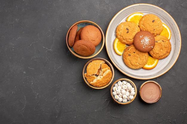 Draufsicht köstliche kekse mit frisch geschnittenen orangen auf dunklem hintergrund keksfrucht süßer kuchen keks zitrus