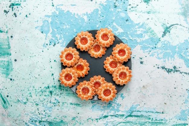 Draufsicht köstliche kekse mit marmelade in schwarzer platte auf dem blauen schreibtischkekskeks süßer zuckerfarbentee