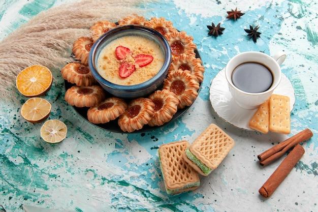 Draufsicht köstliche kekse mit marmelade tasse kaffee und erdbeerdessert auf hellblauer oberfläche