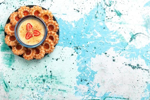Draufsicht köstliche kekse mit marmelade und erdbeerdessert auf dem süßen kekszucker des hellblauen hintergrundkekszuckers