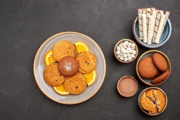 Draufsicht köstliche kekse mit pfeifenkeksen und orangen auf dunkler oberfläche fruchtkeks dessert zitrus keks süß