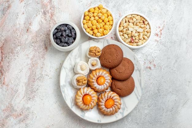 Draufsicht köstliche kekse mit süßigkeiten und nüssen auf weißem hintergrund keks süße kuchen keksnuss