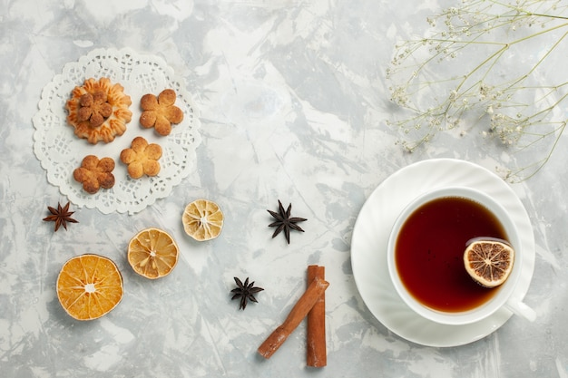 Draufsicht köstliche kekse mit zimt und tasse tee auf den hellweißen schreibtischkekskekszuckersüßteechips