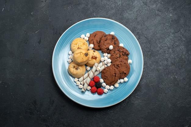 Draufsicht köstliche kekse schokolade und einfache mit süßigkeiten auf dunkelgrauem oberflächenzuckerkekskuchen süßer keks