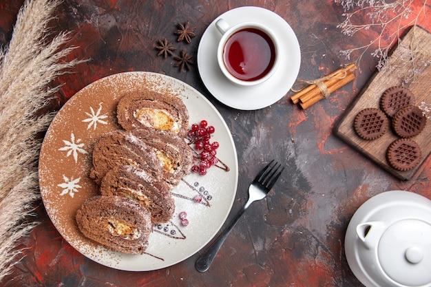 Draufsicht köstliche keksröllchen mit keksen und tee auf dunklem schreibtisch süßer tortenkuchen