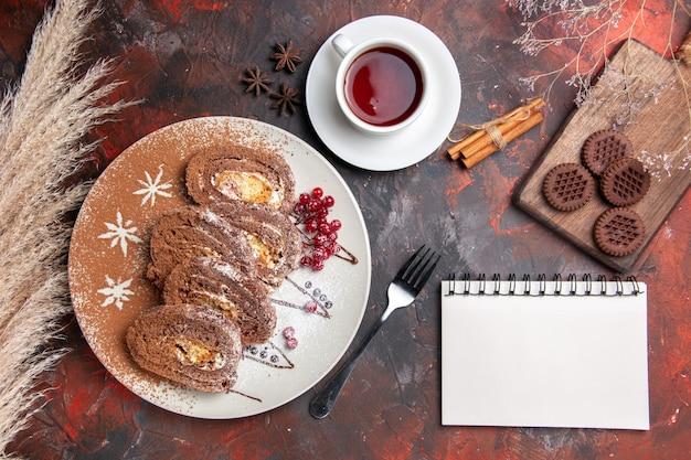 Draufsicht köstliche keksröllchen mit keksen und tee auf dunklem tisch