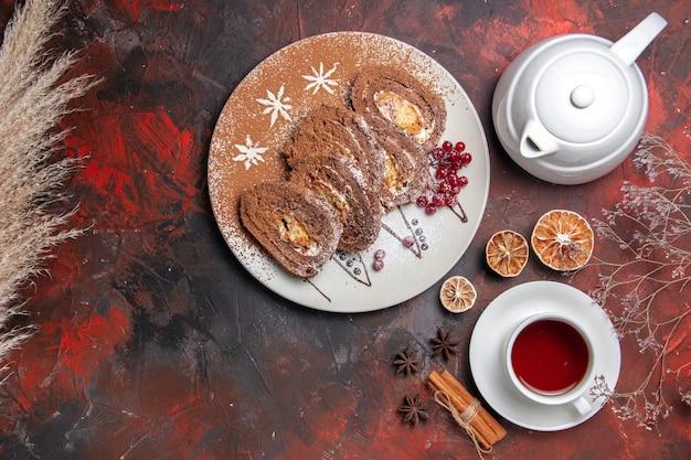 Draufsicht köstliche keksröllchen mit tasse tee auf dunklem tisch