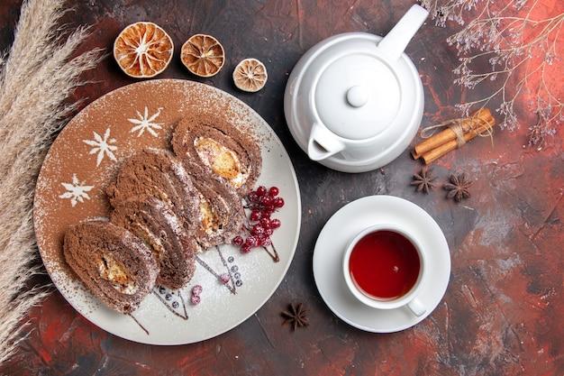 Draufsicht köstliche keksröllchen mit tasse tee auf dunklem tischkuchenkuchen süß