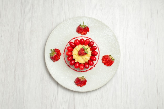 Draufsicht köstliche kleine kuchen mit früchten auf hellweißem schreibtisch