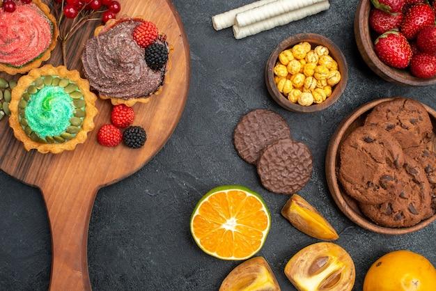 Draufsicht köstliche kleine kuchen mit keksen und früchten auf einem dunklen tisch süßer tortenkuchen