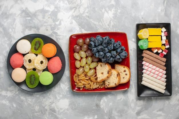 Draufsicht köstliche kleine kuchen mit trauben und keksen auf weißer oberfläche kekszuckerkuchen süßer kuchen tee-keks