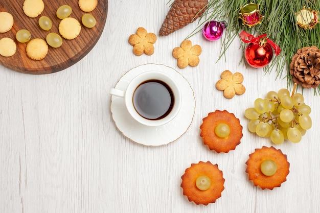 Draufsicht köstliche kleine kuchen mit trauben und tasse tee auf weißem schreibtischkuchenkuchen-tee-keksplätzchen