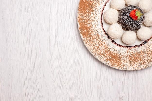 Draufsicht köstliche kokos-bonbons mit schokoladenkuchen auf weißem hintergrund zuckerkuchen keks süße süßigkeiten kekse