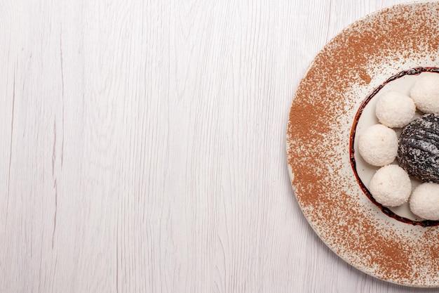 Draufsicht köstliche kokosbonbons mit schokoladenkuchen auf weißem schreibtisch zuckerkuchenkeks süße süßigkeiten