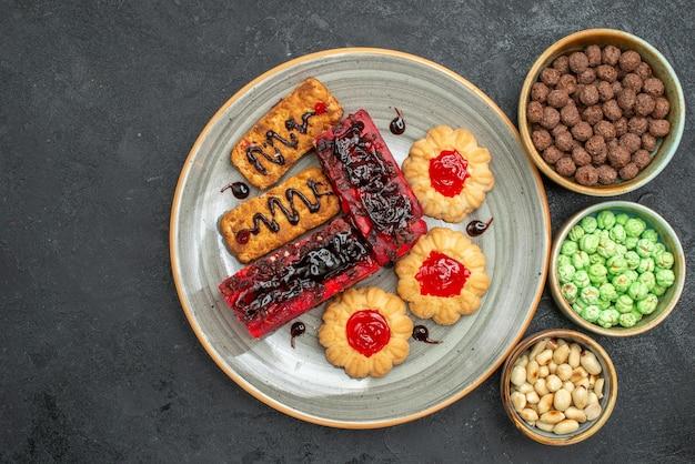 Draufsicht köstliche kuchen fruchtige süßigkeiten mit keksen und bonbons auf dunklem hintergrund zuckerplätzchenkuchen süßer kuchenteekeks