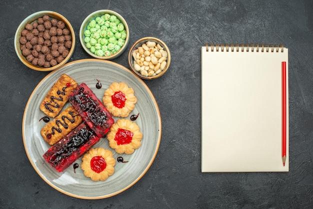 Draufsicht köstliche kuchen fruchtige süßigkeiten mit keksen und nüssen auf dem dunklen hintergrund zuckerkeks-keks-kuchen süße torte Kostenlose Fotos