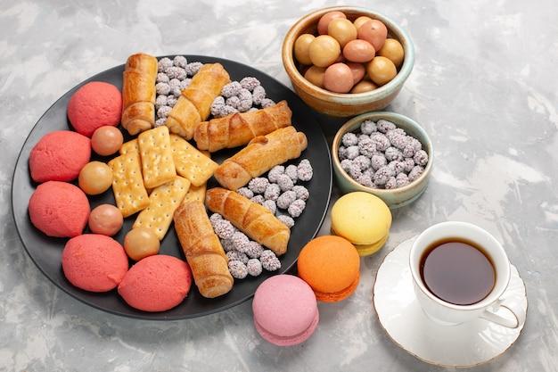 Draufsicht köstliche kuchen mit bagels cracker bonbons und tee auf hellweißem schreibtischkuchen kekskeks süßer zuckerkuchen