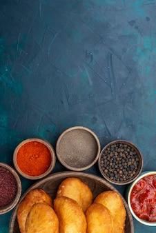 Draufsicht köstliche kuchen mit fleischfüllung in braunem teller mit gewürzen auf dunkelblauem schreibtisch teigkuchen brötchen essen