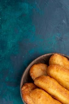 Draufsicht köstliche kuchen mit fleischfüllung innerhalb der braunen platte auf dunkelblauem hintergrundteigkuchenbrötchenfutter